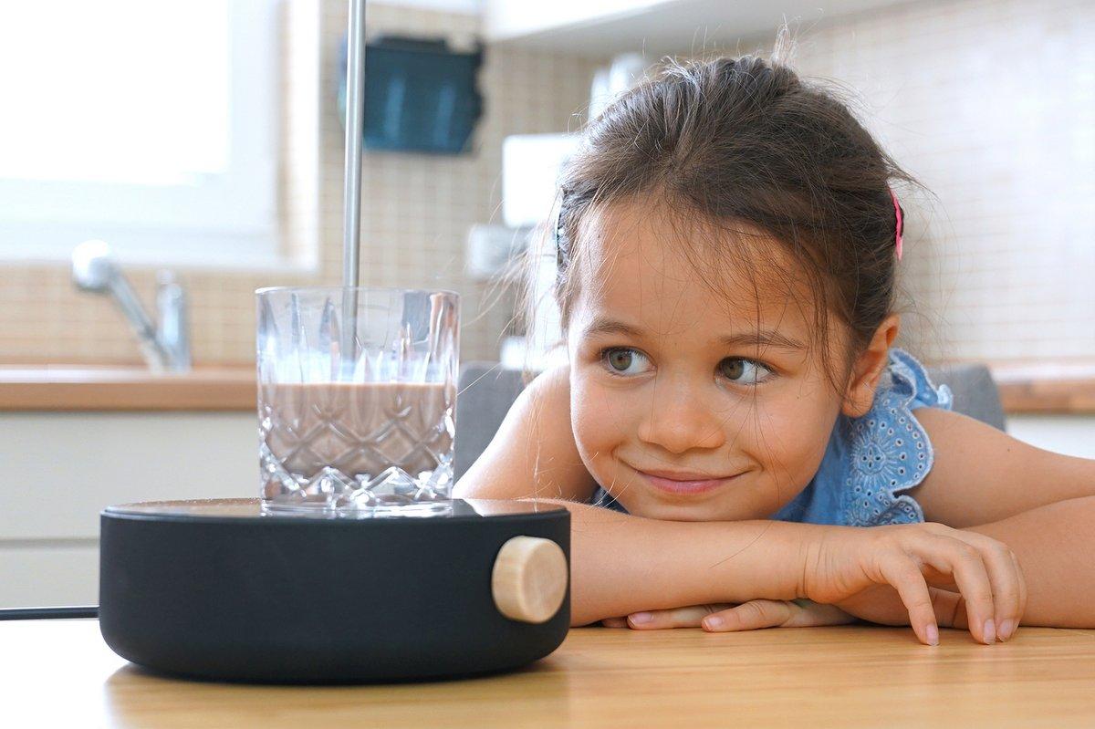 Kind mit Kakaoglas und Heatle in der Küche