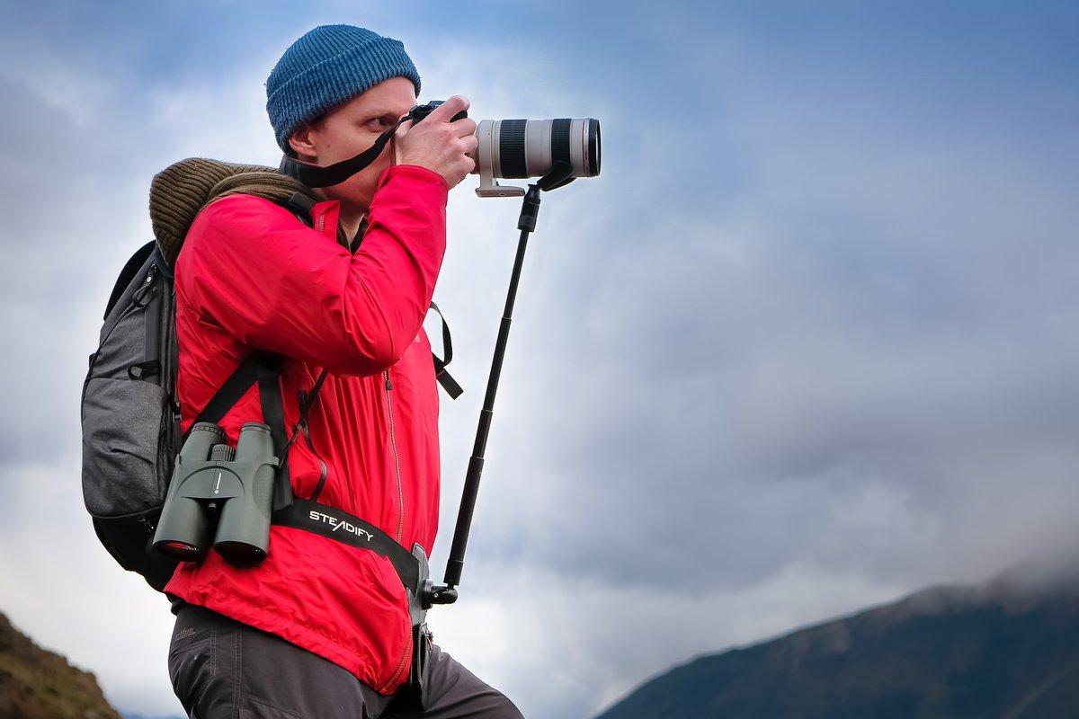 Mann in roter Outdoorjacke fotografiert