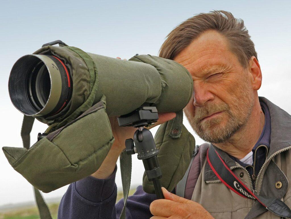 Mann beobachtet mit einem Spektiv