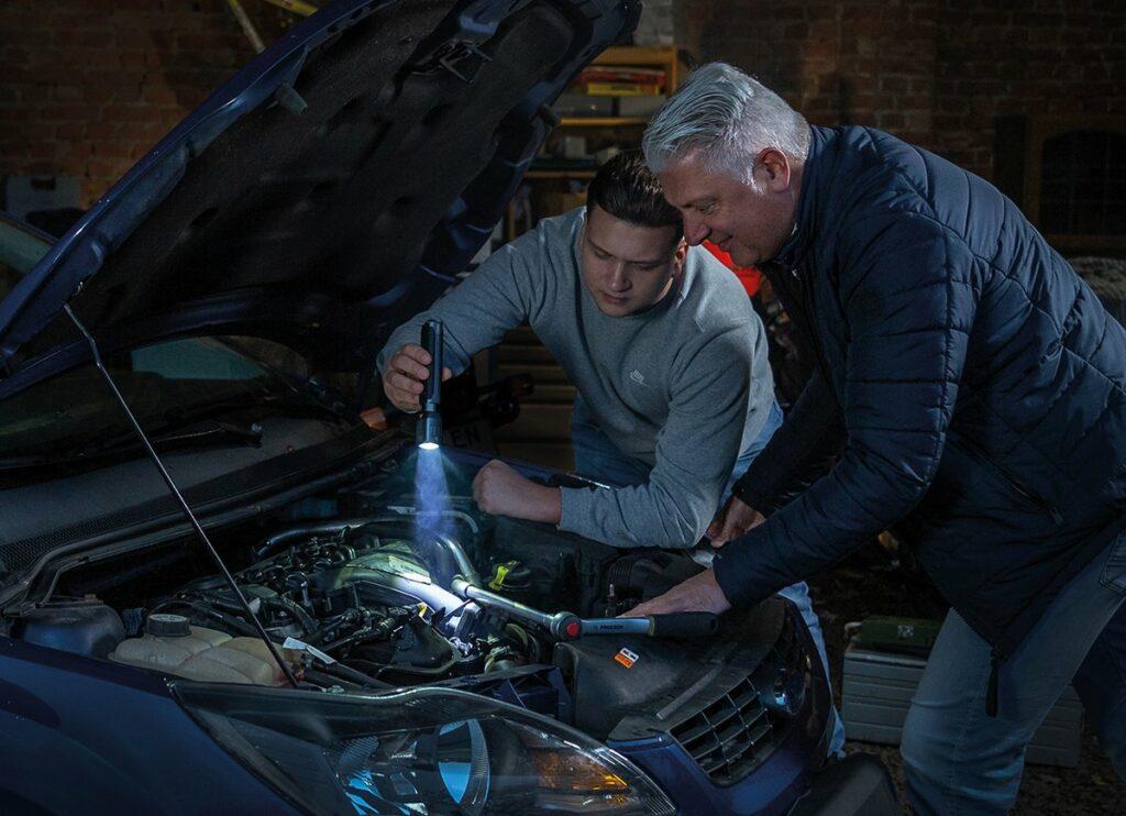 Zwei Männer reparieren etwas am Auto am Motor im dunklen. Haben eine Taschenlampe.